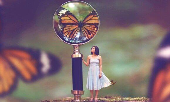 Mulher e lupa mostrando borboleta