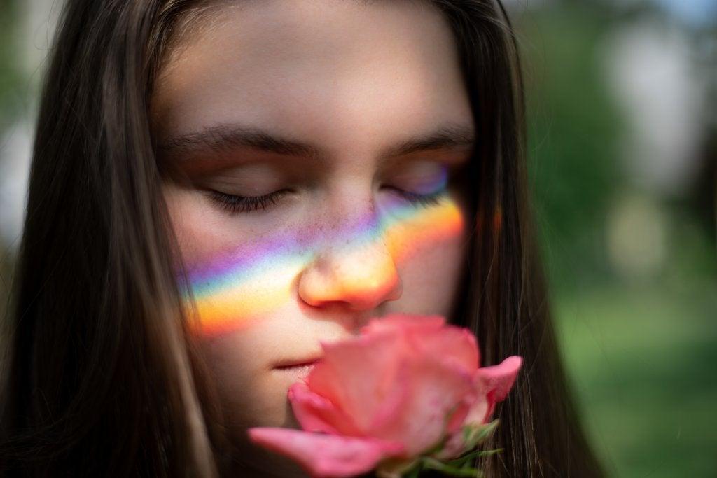 Jovem sentindo aroma de flor