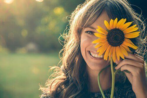 Mulher com um sorriso e girassol no rosto