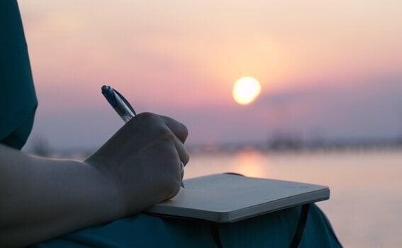 Pessoa escrevendo em diário