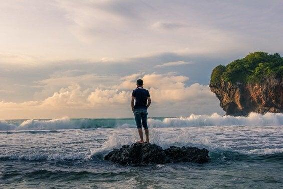 Homem em pedra observando o mar