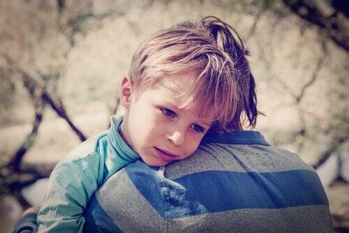 Menino com baixa autoestima abraçando seu pai