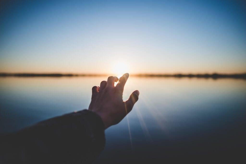 Mão diante do pôr do sol