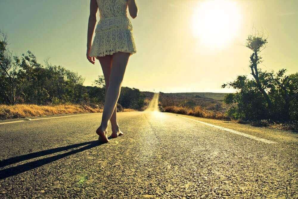 Mulher caminhando sozinha em estrada