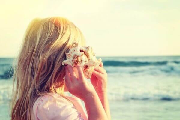 Criança ouvindo concha diante do mar