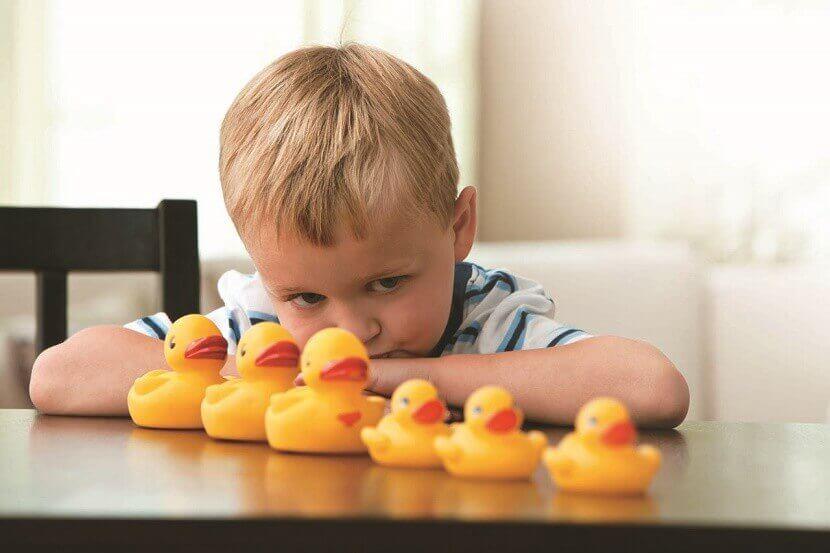 Menino com autismo olhando patos de borracha