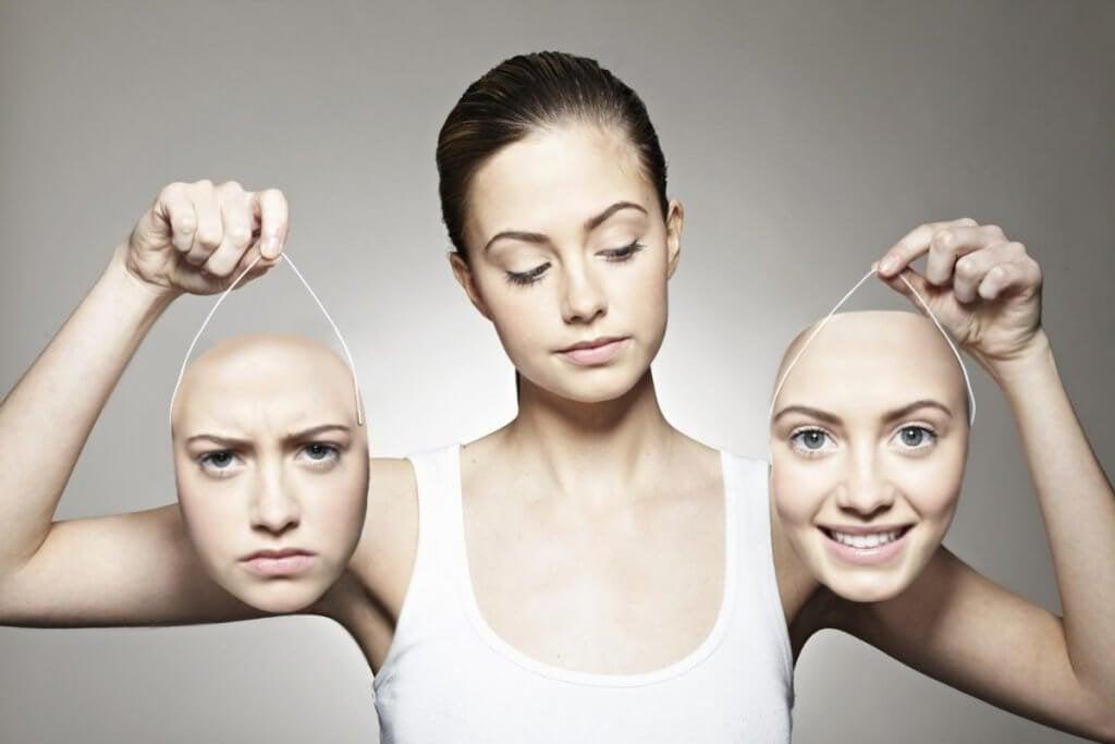 Mulher segurando duas máscaras do seu rosto
