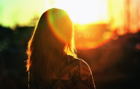 Silhueta de mulher diante do sol