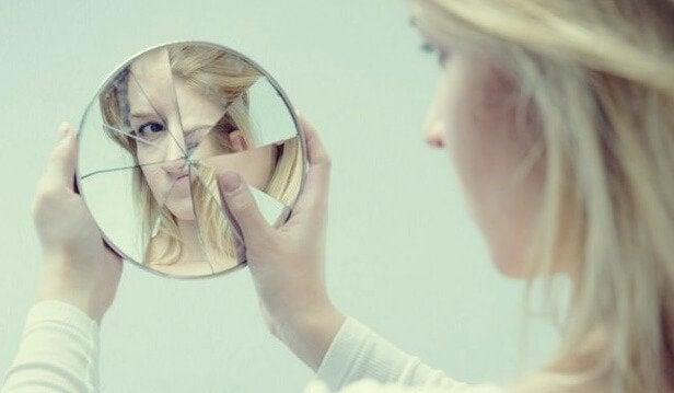 Mulher se olhando em espelho quebrado