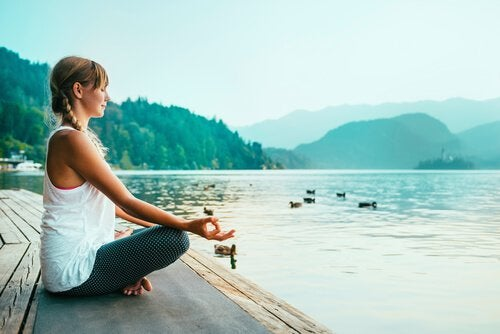Mulher meditando diante de lago