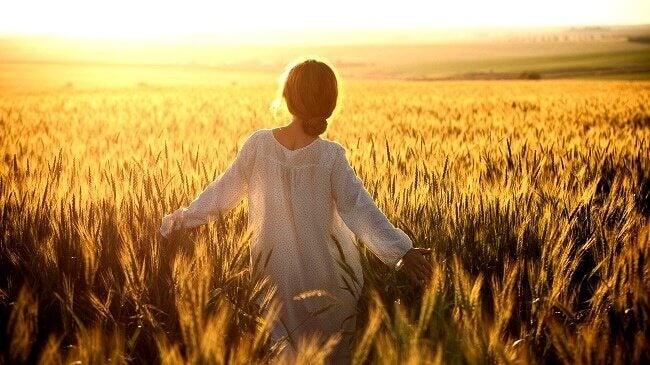 Mulher no campo no pôr do sol