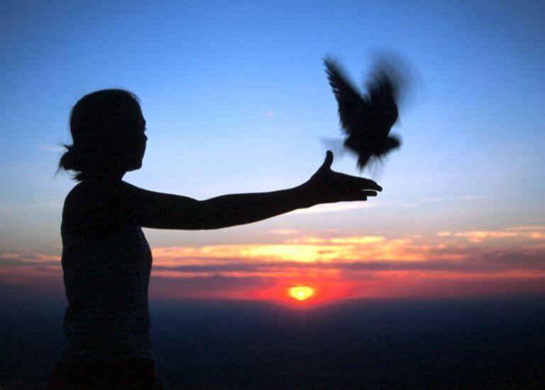 Mulher libertando pássaro