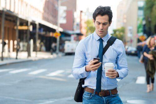 Homem olhando o celular na rua