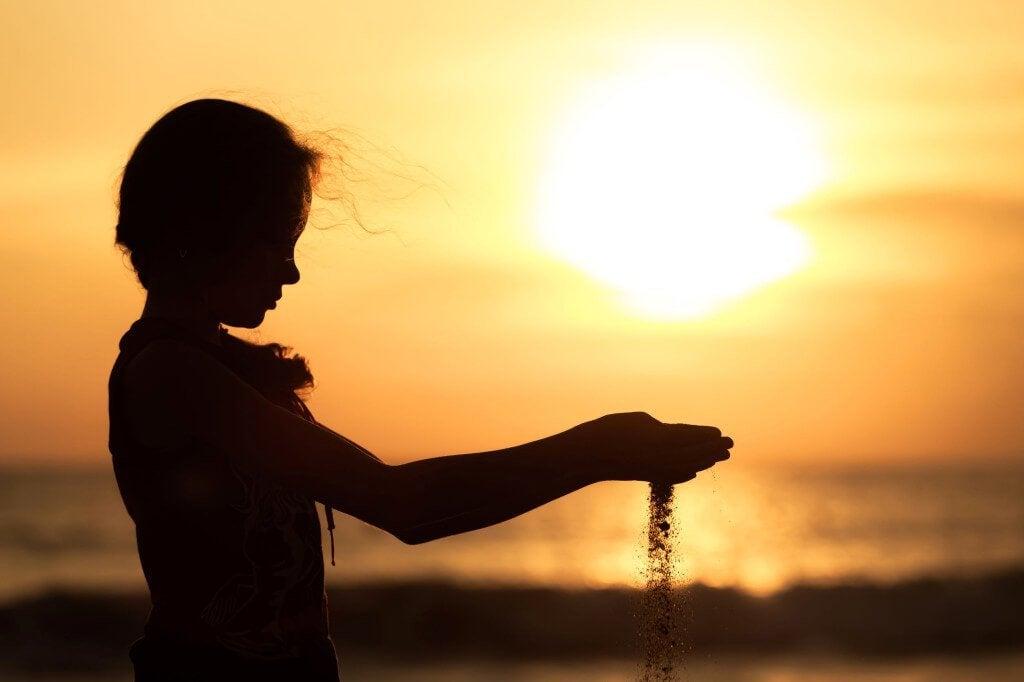 Menina mexendo na areia da praia