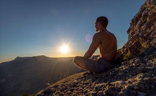 Homem meditando em montanha
