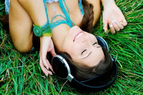 Mulher deitada na grama ouvindo música
