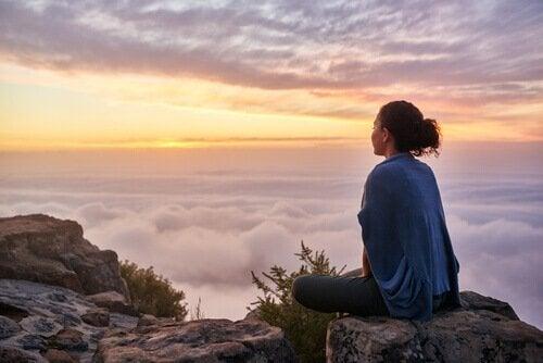 Mulher meditando no topo de montanha