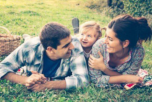 Pais deitados na grama com sua filha