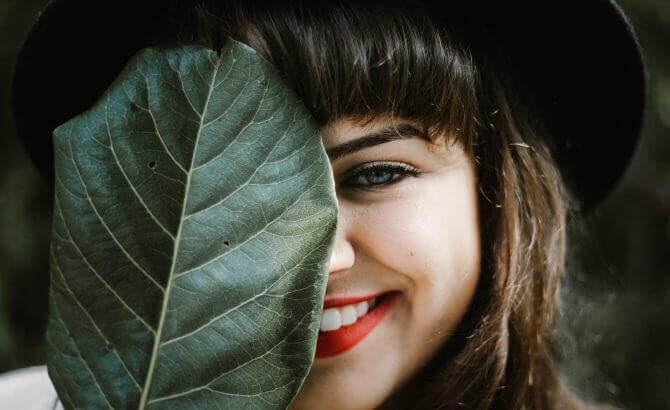 Mulher sorrindo atrás de folha