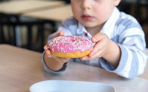 Criança comendo doce rico em açúcar