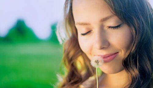 Mulher sentindo aroma de dente-de-leão