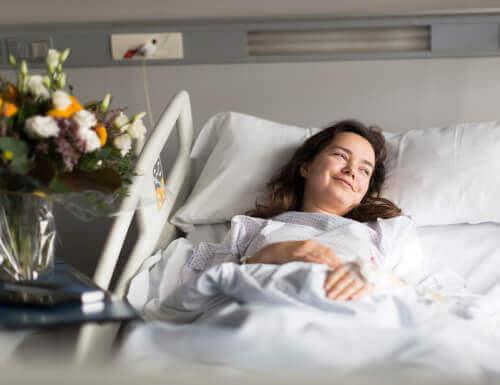 Mulher sorrindo em cama de hospital apesar de doença