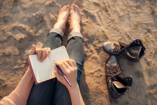 Mulher escrevendo diário na praia