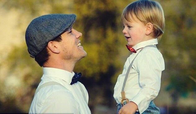 Pai sorrindo para o filho pequeno