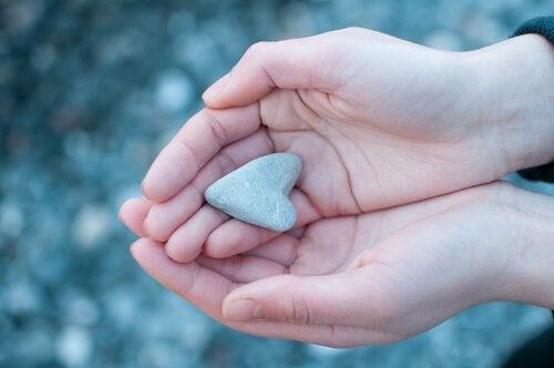 Mãos segurando coração de pedra