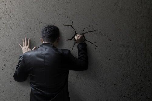 Homem com raiva socando a parede