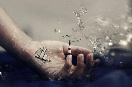 Mão com barco e farol
