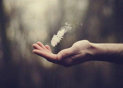 Mão com pluma flutuando