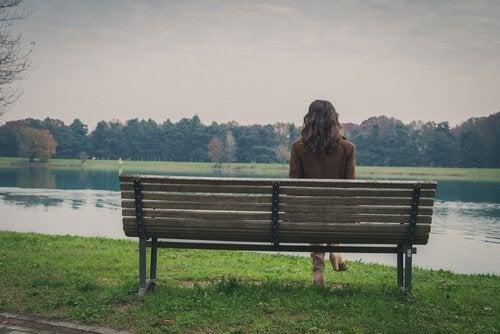 Mulher sentada diante de lago