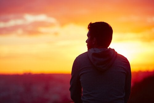 Homem contemplando o pôr do sol