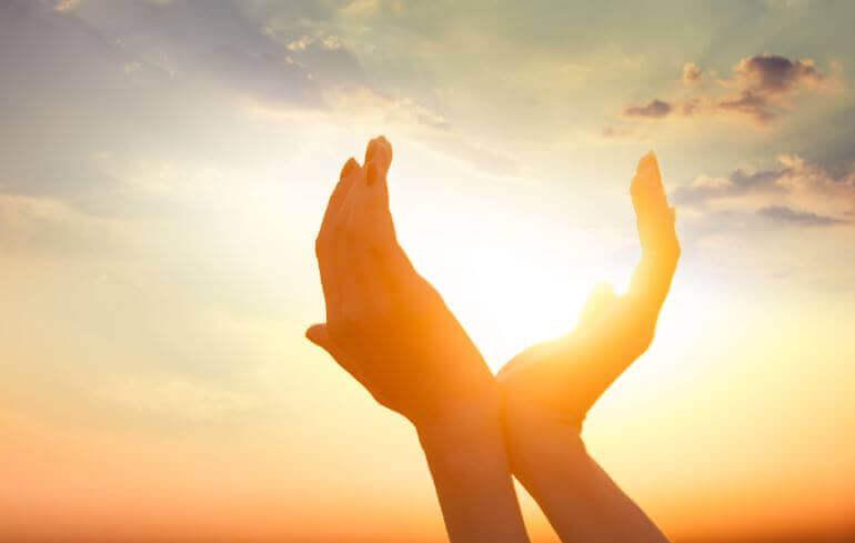 Mãos abertas em torno do sol