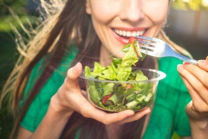 Mulher sorrindo comendo salada