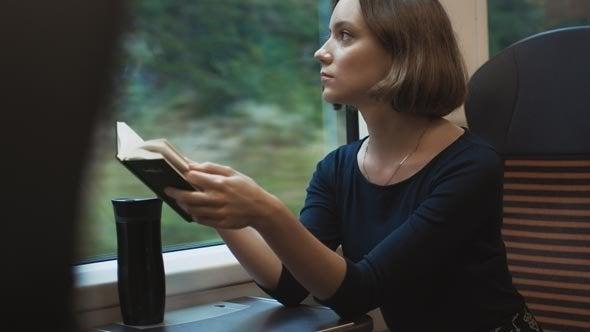 Mulher lendo em trem enquanto viaja