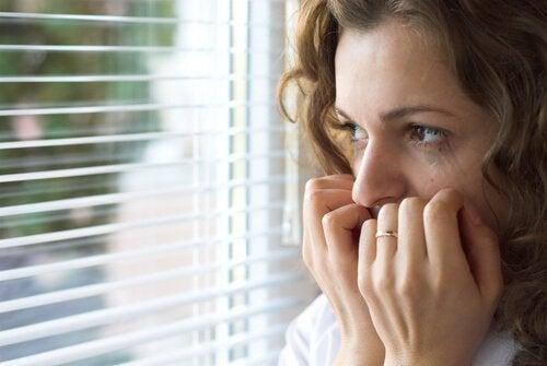Mulher nervosa olhando pela janela