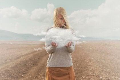 Mulher segurando uma nuvem em um deserto
