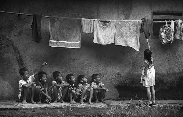 Crianças embaixo de um varal de roupa