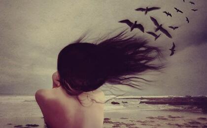 Mulher na praia com vento e pássaros
