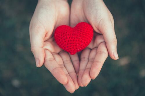 Mão segurando coração de crochê