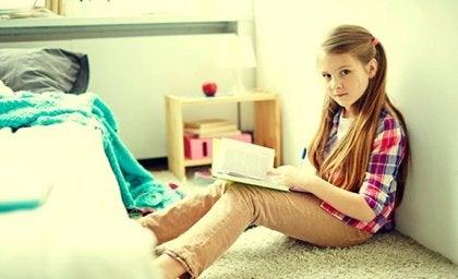 Menina lendo um livro em seu quarto