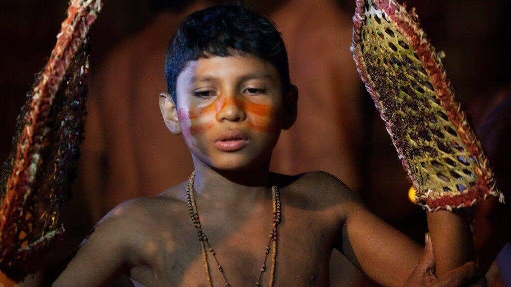 Criança indígena participando de ritual