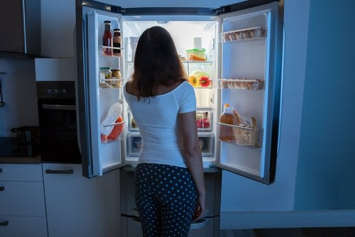 Mulher assaltando a geladeira à noite