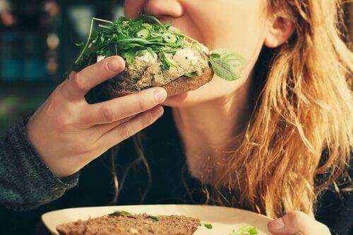 Mulher comendo sanduíche