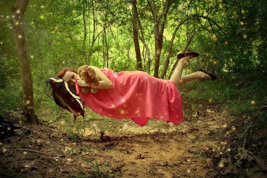 Mulher dormindo flutuando em floresta