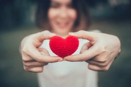 Mulher segurando coração de crochê
