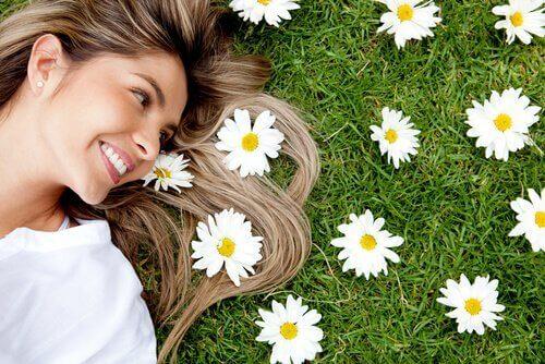 Mulher deitada na grama com flores