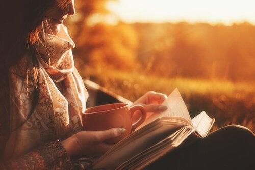 Mulher tomando café e lendo um livro